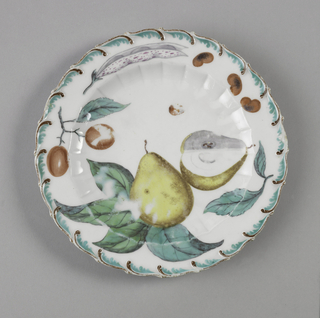 Scalloped circular form with brown and aqua foliate scroll.  Foliage includes a pear, plums, kidney beans, and beans in a pod.