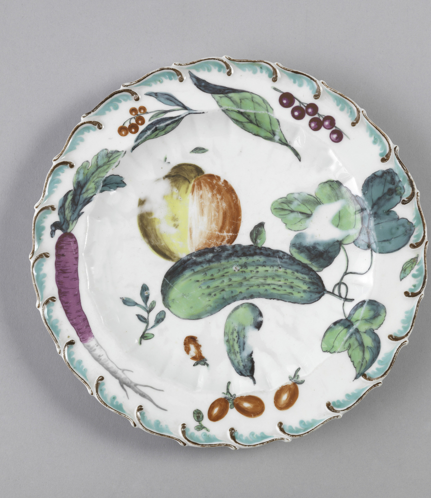Scalloped circular form with brown and aqua foliate scroll.  Foliage includes a peach, a carrot, cucumbers, tomatoes and berries.
