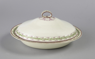 Deep oval dish with molded edge to receive domed cover with flattened ring on top. Overglaze painting in green and rose purple: border of twin ears of grain and green leaves between lines around edges of bowl and cover and on ring. Finely veined purple leaves clustered around ring.