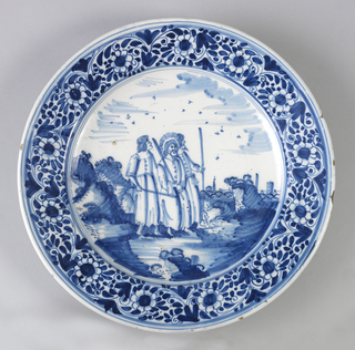 Circular plate with wide rim, resting on short foot ridge; painted in underglaze blue on white with a scrolled floral border on rim and in center withscene of 3 men with staffs in landscape (Christ and disciples on road to Emmaus).