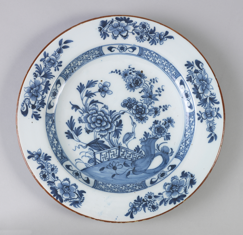 Circular plate with wide rim; painted in underglaze blue on white with brick-red outer border; center has chinoiserie scene of bird, flowers; cavetto has diaper pattern with 5 floral reserves; outer rim has 5 floral sprays; back painted with 4 evenly-spaced squiggles.
