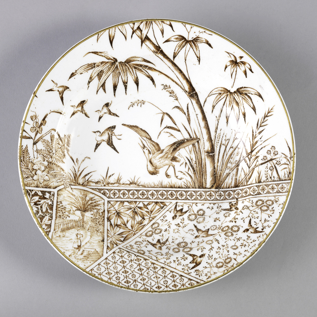 Circular in form, the white ground with brown transfer-printed decoration, the top section showing birds (cranes?) in flight in a landscape, the lower section composed of differently shaped panels of Japanese-inspired motifs including flowers, birds and geometric patterns.  Gilt rim.