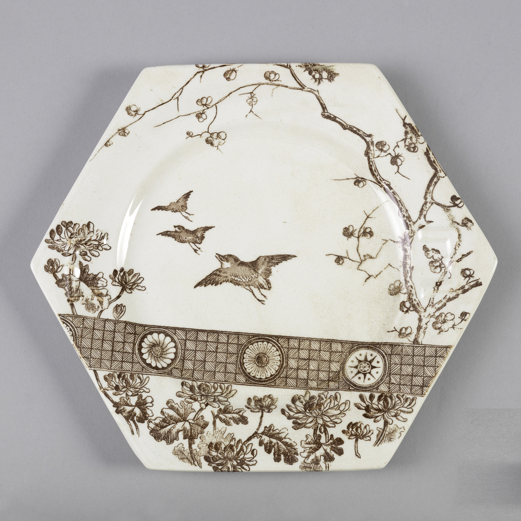 Six-sided form with circular caveto, the cream-colored ground with brown transfer-printed decoration of three birds in flight among a tree and flowers, above a geometric-patterned band and a section with flower decoration.