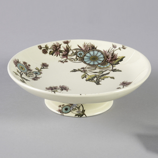 Circular dish on flaring circular foot, the white ground decorated with Japanese-inspired polychrome transfer-printed decoration of sprays of naturalistic flowers with superimposed medallions showing birds in flight or stylized flowers.