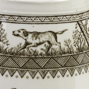 Of slightly conical form with circular mouth and short pinched spout, the rectangular  handle with curved corners.  Cream-colored body with brown Japanese-inspired transfer printed deocration: wide band just under mouth showing panels of geometric decoration and two landscapes with either hunting dog or birds; on either side of pitcher is an oval ring of flowers, buds and leaves surrounding a medallion with abstract leaf-and-stem pattern; geometric pattern along back of handle.