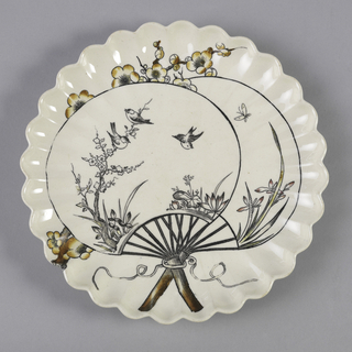 Circular form with up-curved lobed rim, the cream colored ground with Japanese-inspired transfer printed decoration in black and tones of brown and yellow showing two fans with scenes of birds and a butterfly among flowering plants and branches; the fans superimposed over a flowering branch, a flowing ribbon encircling the handles.