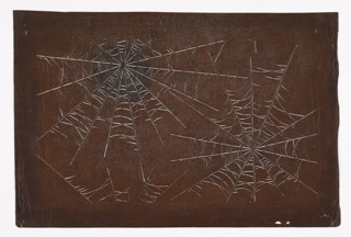Two spirderwebs and a partial third are depicted. The design is created using very thin stripes carved out suggesting the delicacy of the webs. There is a dark stain on the top left spiderweb and small holes on the bottom right corner.
