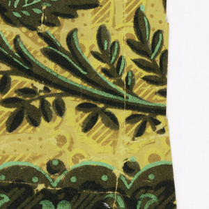 Irise or rainbow paper. Scrolling vine with stylized floral and foliate motifs. Printed in green flock and overprinted with two shades of green. The background shades from pink to yellow. Band of floral rosettes and dentil at lower edge.