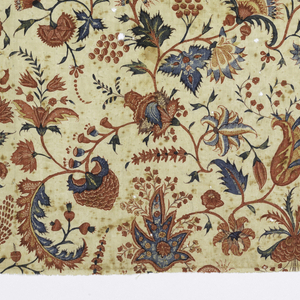 Finely woven cotton with an all-over, repeating floral design of small sprays of exotic flowers and foliage in many colors on a white ground. Strong reds in the blossoms with yellow, blue and green in the foliage, with fine filling patterns within leaves or flowers, as minute white flower sprays within a red leaf or tiny red flowers on a dark green leaf. Original glaze is still present but now dark with age.