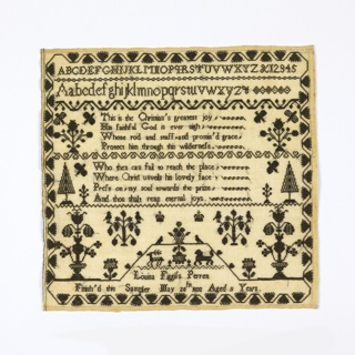 Embroidered entirely in black on a white ground. Bands of alphabets and verses, and an inscription, are separated by floral cross borders. Isolated motifs of trees, urns of flowers, and birds are symmetrically arranged on either side. The composition is framed on four sides with a stylized strawberry vine border.