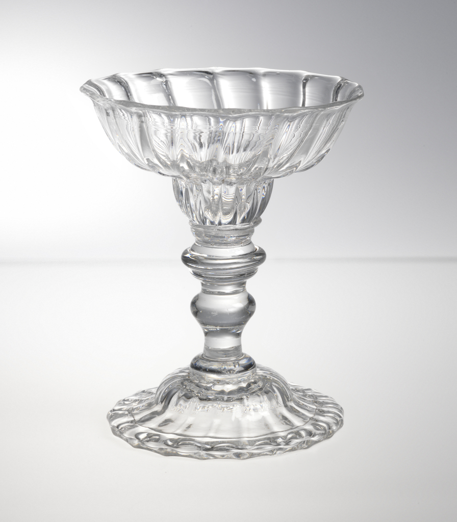 Double ogee-shaped bowl, ribbed, on tall multi-knopped stem; domed, ribbed base, folded over at edge; pontil mark base.