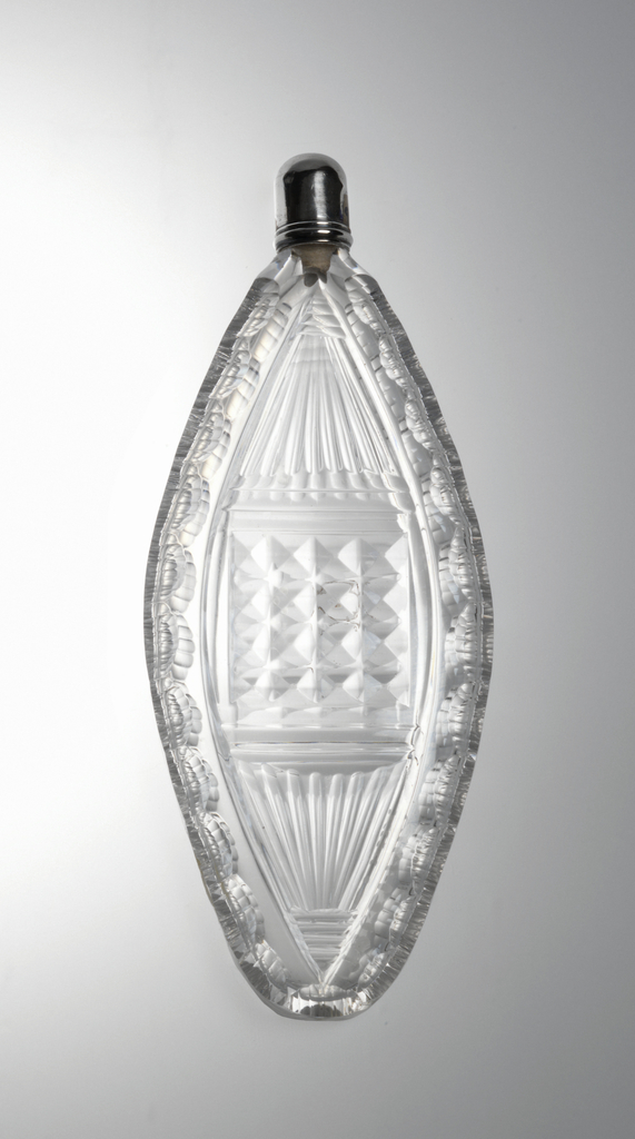 Flattened ovoid body cut on each side with central panel of diamonds, rayed fluting either side, cut around the side with 2 rows of ridged printies, threaded neck, stopper; silver cap.