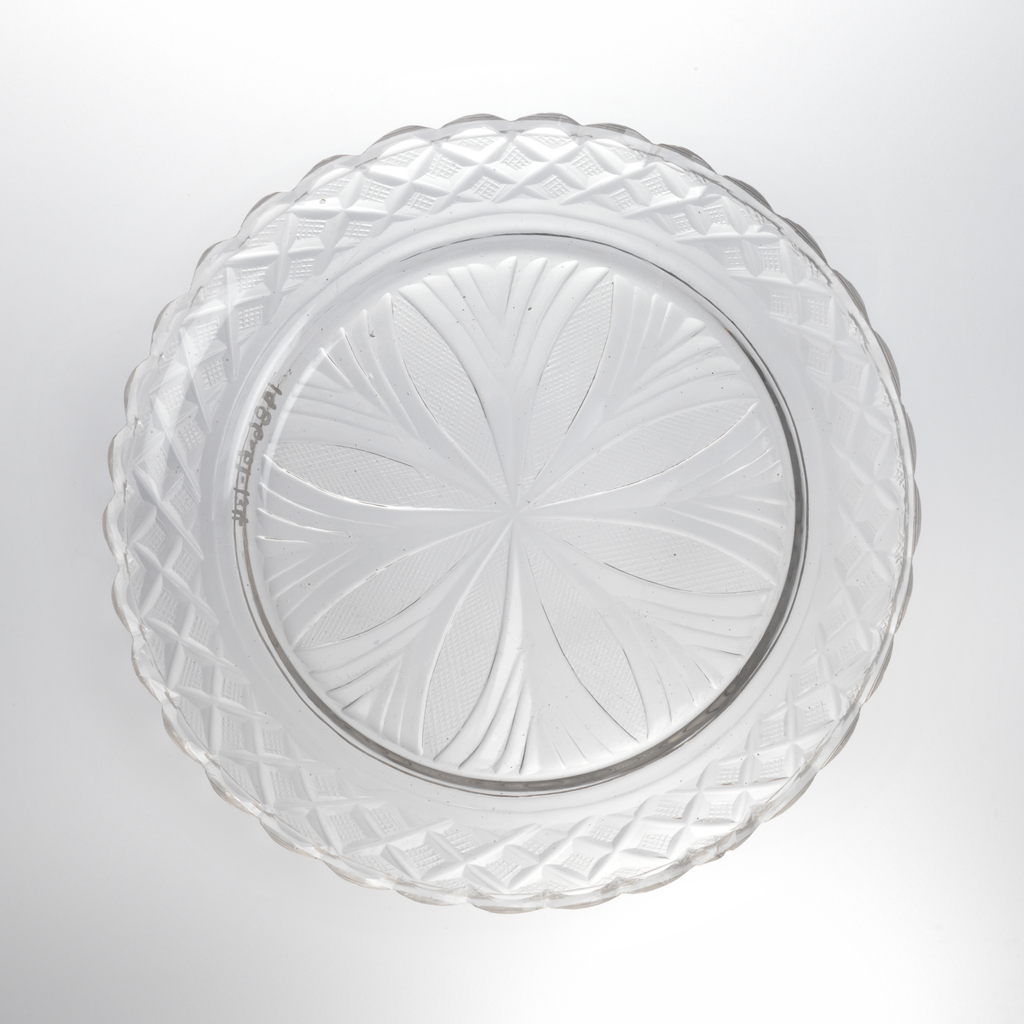 Circular plate with wide up-turned rim; center cut with radial pattern of petals filled in with fine diamonds, fans in between; rim cut with strawberry diamonds and scalloped edge; glass bubbly.