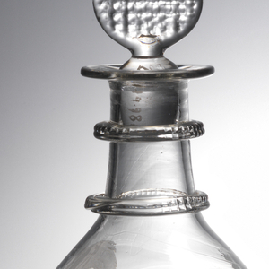 Bulbous, lightly blown body, 2 neck rings-knotched, everted lip, row of faint molded vertical fluting bottom of sides, above engraved with a rose, thistle and shamrock; target shaped stopper with waffle pattern; bottom: pontil mark surrounded by maker's mark (faint) and light fluting to edge.