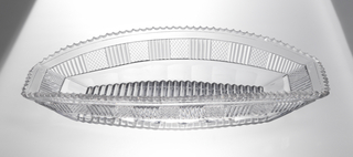Oblong, boat shape dish with flared sides and squared ends. Sides cut with band of alternating panels of fine diamonds and flutes. Fluted bottom. Inverted scallop rim.