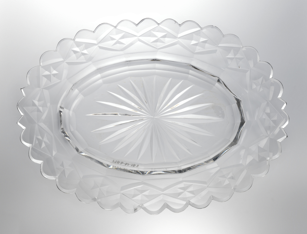 Oval dish with wide rim scalloped at the edge, star cut at center, cavetto with facets, rim cut with flat diamond pattern, glass clear and heavy.