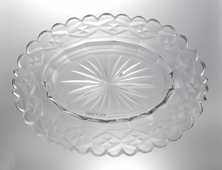 Oval dish with wide rim scalloped at the edge, star cut at center, cavetto with facets, the rim cut with flat diamond pattern, glass clear and heavy.