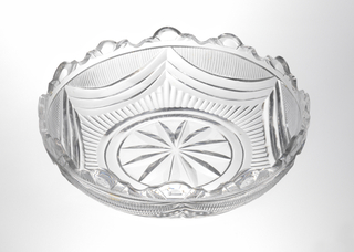 Shallow, circular bowl, encircled star cut on bottom, narrow flutes rise to swags filled in with fine flutes. Trefoil cut rim, well defined cuts.