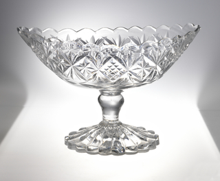 Oval-shaped bowl with scalloped rim, on the sides a wide band of shallow diamonds filled with small diamonds or stars, a row of husks beneath; inverted baluster-shaped stem, high, spreading lobed foot with scalloped edge; molded star bottom side.