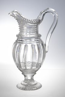 Round body on splayed circular foot, tapered neck, scalloped lip with pouring spout, loop handle; sides cut with wide pillar flutes, prism cutting on neck and below it faceted stem and slightly domed foot, bottom of foot cut with radiating flutes.