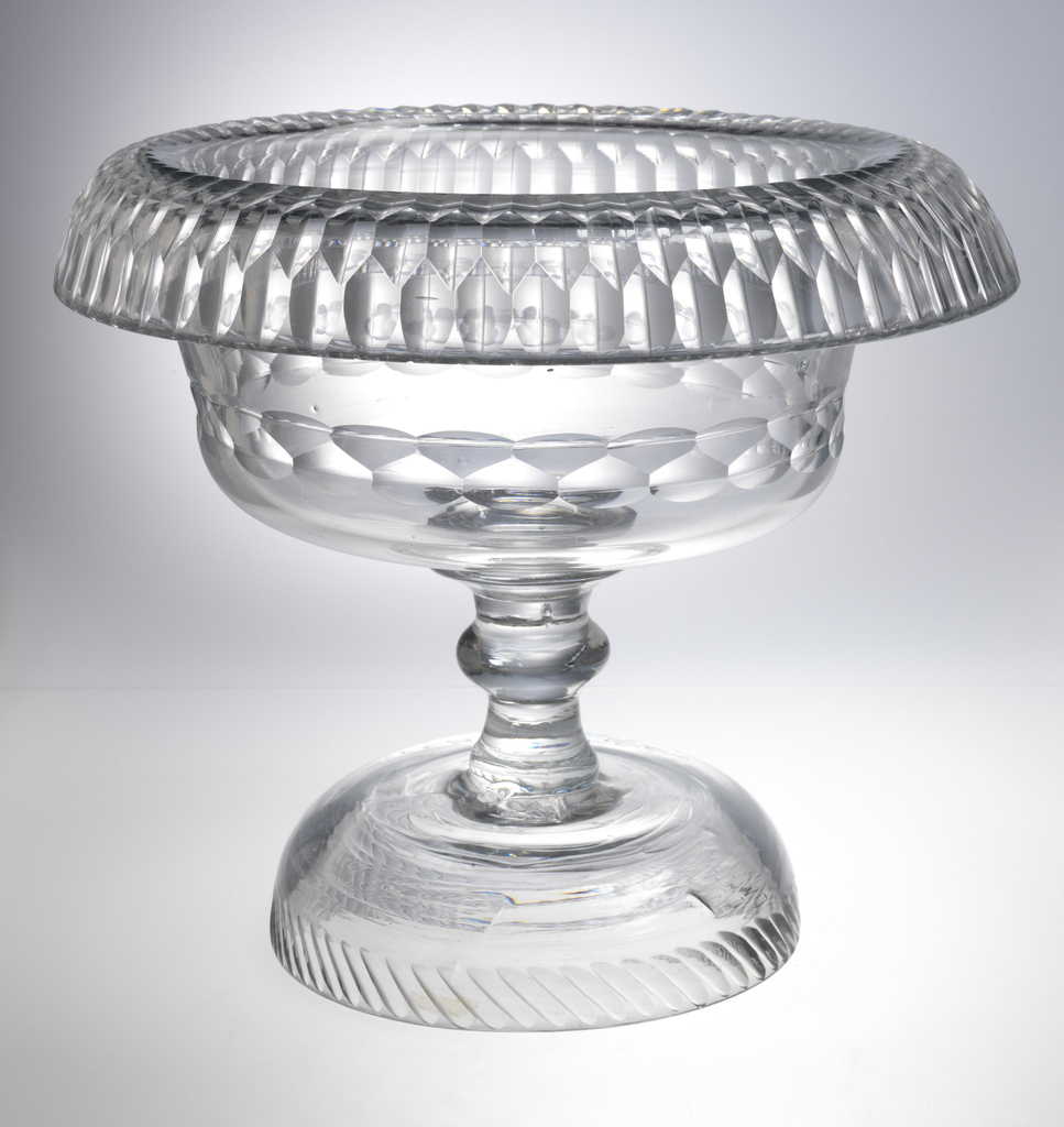 Round bowl with large turned-over rim, sits on tall stem with central knop, high domed base with cut blazes at bottom edge; sides of bowl cut with double band of facets, a triple band of facets on over-turned rim; pontil mark bottom; glass dark clear.