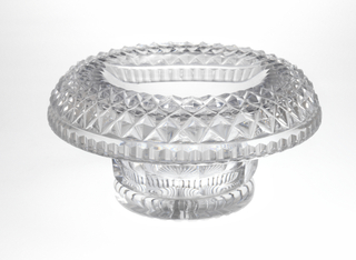 Cylindrical bowl with straight faceted sides rising to large turned-over rim covered with diamond cutting and faceted around the edge; bottom star cut.