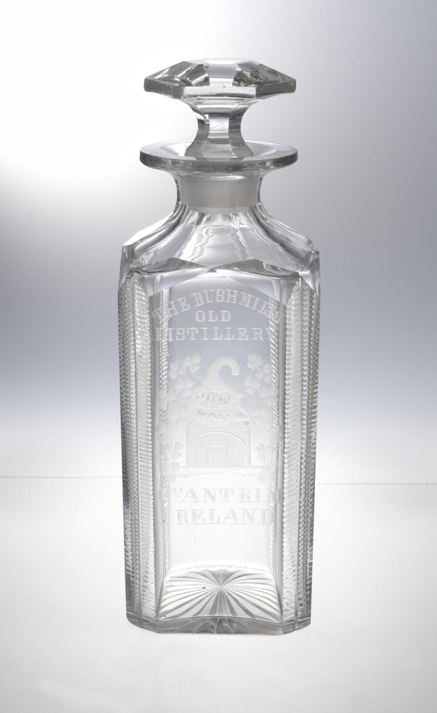 """Square-sided body with chamfered corners cut with fine horizontal blazes, shoulder cut with wide flutes, wide lip; one side engraved with """"The Bushmill Old Distillery, Co. Antrim, Ireland, """" and a picture of the distillery marked """"pure malt"""" surrounded by shamrocks; bottom cut with star; stopper mushroom-shaped with hexagonal faceting."""