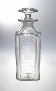 "Square-sided body with chamfered corners cut with fine horizontal blazes, shoulder cut with wide flutes, wide lip; one side engraved with ""The Bushmill Old Distillery, Co. Antrim, Ireland, "" and a picture of the distillery marked ""pure malt"" surrounded by shamrocks; bottom cut with star; stopper mushroom-shaped with hexagonal faceting."