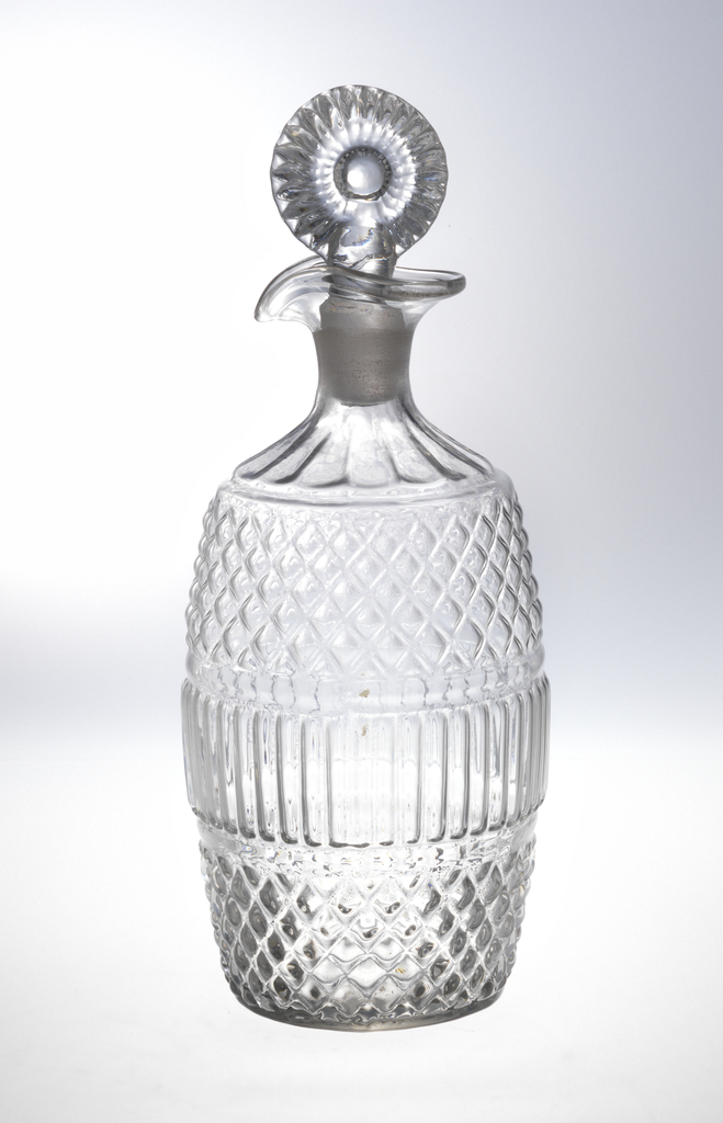 3-part molded blown, barrel-shaped body. Central band of vertical flutes, diamond pattern above and below, fluted shoulder to neck everted slip with pouring spout, molded fluted bulls-eye stopper.
