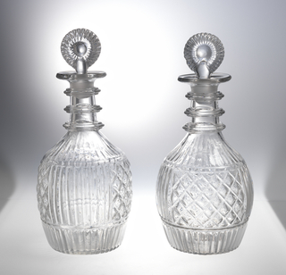 3-part mold blown (very hard to see), bulbous body with central panel in alternate sections of vertical fluting and diamonds, fluting above and below, 3 triple neck rings, wide lip, molded fluted bulls-eye stopper (replacement; pontil mark bottom.
