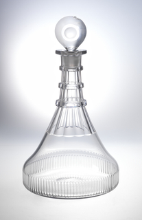 """Ship's decanter"" type. Broad, flat base with cut comb flutes. Long tapered flutes interrupted by 3 flat neck rings. Flat projecting lip. Cut target stopper, with fluted neck."
