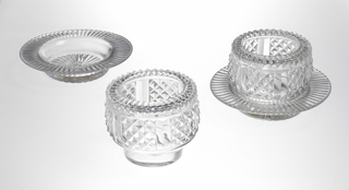 Round body on short foot, lip turned-in and cut with fluting, sides cut with 6 panels of diamonds; stand is shallow dish with wide lip cut with flutes, rayed flutes cut on bottom.