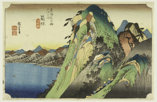 Left, large lake with foothills and white peak of Fuji in the distance. Right, group of precipitous cliffs of many colors. Heads of pilgrims can be seen.