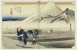 Fuji rising from a group of lower peaks on the far side of rice fields; its peak going above the upper line of the frame line. In the foreground, two women and a porter pass along the road to the left. Two cranes in the rice field.