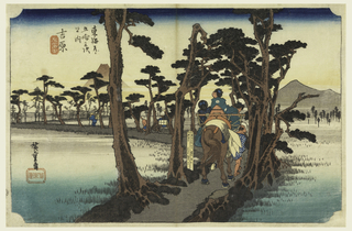 Horse with three women in balanced saddle, led by man, pass along road edged with pine trees. Left, Fuji in distance. Right, peaks of other mountains.