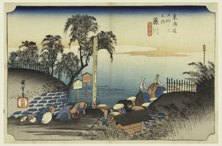 Villagers bowing down as head of daimyo procession reaches the entrance of village. On either side of road, walled bank with trees and bamboos. Lower center, rice fields.