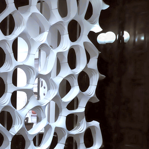 Modular open-work tile structure made of recycled plastic and coated with titanium dioxide.