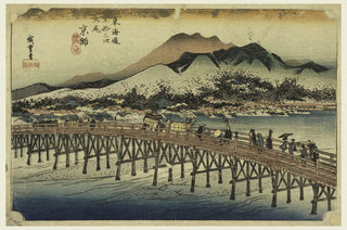 Lower half, long trestle-bridge with people crossing. Upper half, city lies along river bank at foot of range of many-peaked hills and mountain range.
