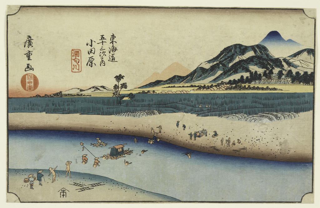 View of river with mountains on right; farmers working across the river and rice fields in the middle distance.