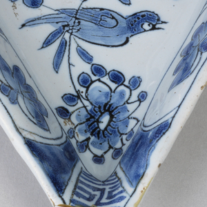Heart-shaped dish on short foot rim with slightly flaring sides; painted inunderglaze blue on white with birds and flowers in center, on sides with alternating panels of flowers and pseudo-Chinoiserie characters.