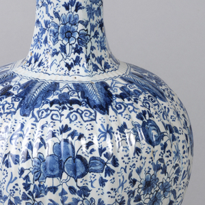 Tall reeded, eight-sided vase, straight-sided base swells to bulbous body, long thin neck, small bulbous section top, flaring mouth; painted in underglaze blue on white with overall floral pattern, lambrequin border bottom, leaf border top of bulbous body section.