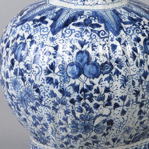 Tall, reeded, eight-sided vase, straight-sided base swells to bulbous body, long thin neck, bulbous section top, flaring mouth; painted in underglaze blue on white with overall floral pattern, lambrequin border base, leaf border top bulbous section of body.