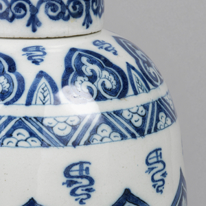 Ovoid body, short straight-sided neck; painted in underglaze blue on white, with Chinese cloud collar band around center, surrounded by stylized leaf border bottom, diaper and leaf border top, pseudo-Chinese squiggles inter- spersed; straight-sided cover, painted with scroll and flowers.