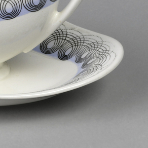 White porcelain sauce boat decorated below rim with concentric black loops all around border on light blue ground, same on dish.