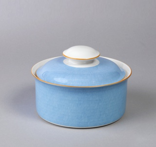 Glazed porcelain power blue bowl and lid with orange rim. Straight-sided bowl with everted rim; mushroom-shaped finial and lid with flared rims.