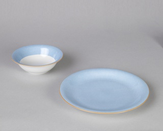 Glazed porcelain blue plate with orange-lined slightly flared rim.