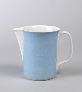 Glazed porcelain blue pitcher with straight sides and flared rim in orange, pointed spout reaching to lower half of body in white; handle in white.
