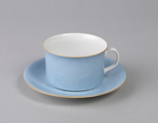 Glazed porcelain blue cup and saucer with orange rims. Cup (a) with straight sides, loop handle and white interior; saucer (b) with impression for cup and lifted flared rim.