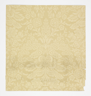 Regular symmetrical pattern vaguely reminiscent of Renaissance brocade; single-motif repeat in off-set vertical columns; highly-stylized bouquet of flowers and leaves sprouting both upward and downward tied at center with ribbons; no attempt at shading; foliage is beige on a darker beige ground.