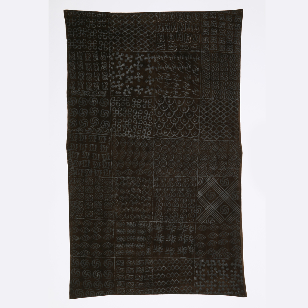Cotton, dyed dark brown and block-printed in a dark glossy substance, in geometric patterns in groups of three rows, forming rectangles. The motifs are carved on calabashes then stamped on fabric in a technique called adinkra.